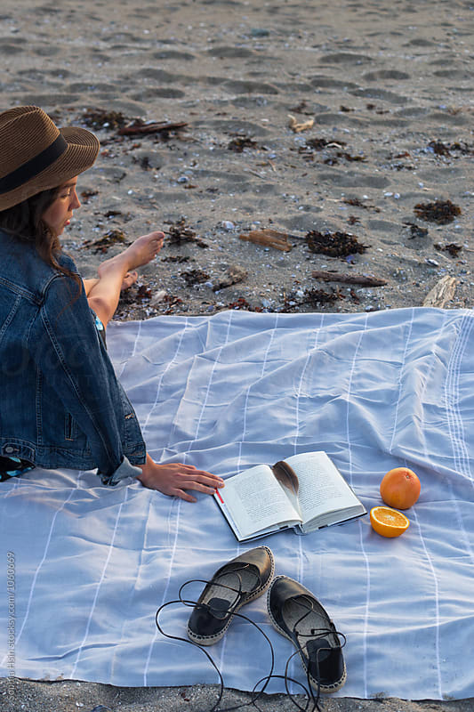 Girl on blanket at the beach by Sophia Hsin for Stocksy United