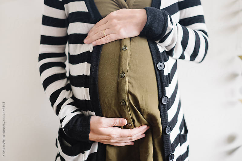 Pregnant woman touching her belly by Kristine Weilert for Stocksy United