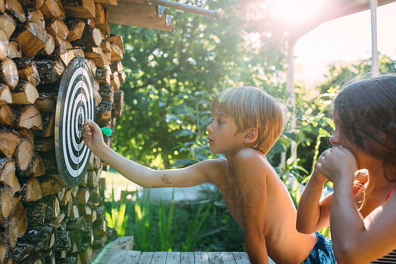 Children playing darts in the yard. by Dejan Ristovski for Stocksy United
