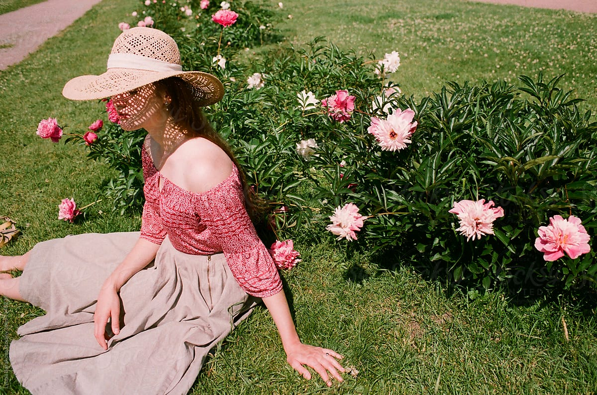 Young Woman Sitting On A Grass Among Flowers Stocksy United