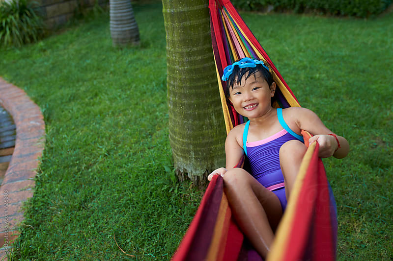 happy little asian girl sitting in the hammock by Bo Bo for Stocksy United