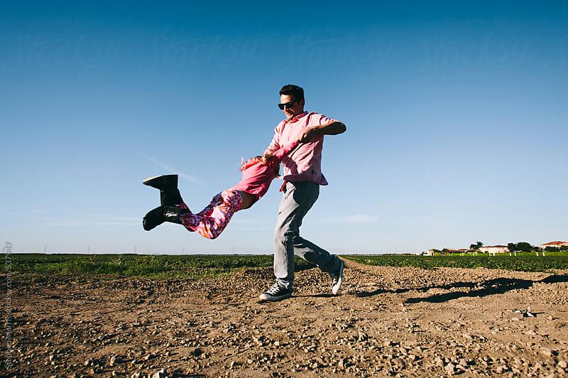 Man swinging girl around by Stephen Morris for Stocksy United