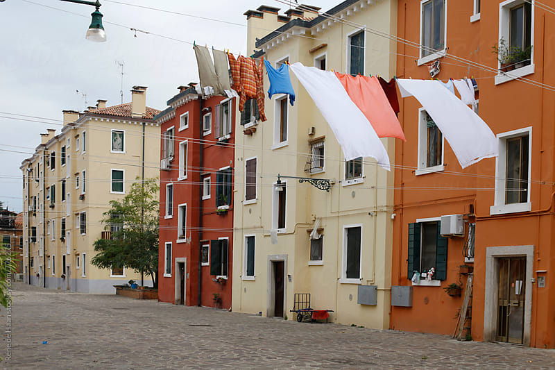 clothes drying on clothesline in between buildings in Venice, Italy by Rene de Haan for Stocksy United
