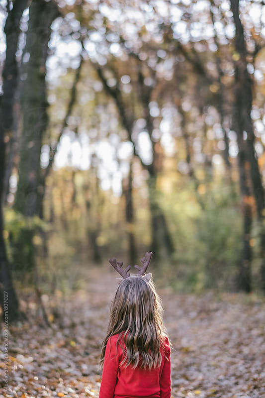 Little Girl with Reindeer Horns Looking to the Woods by Aleksandra Jankovic for Stocksy United