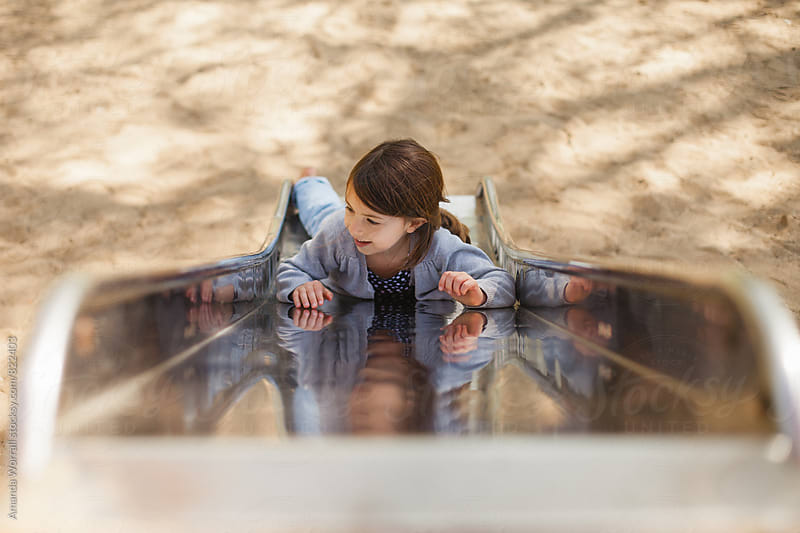 Girl laying on a metal slide by Amanda Worrall for Stocksy United