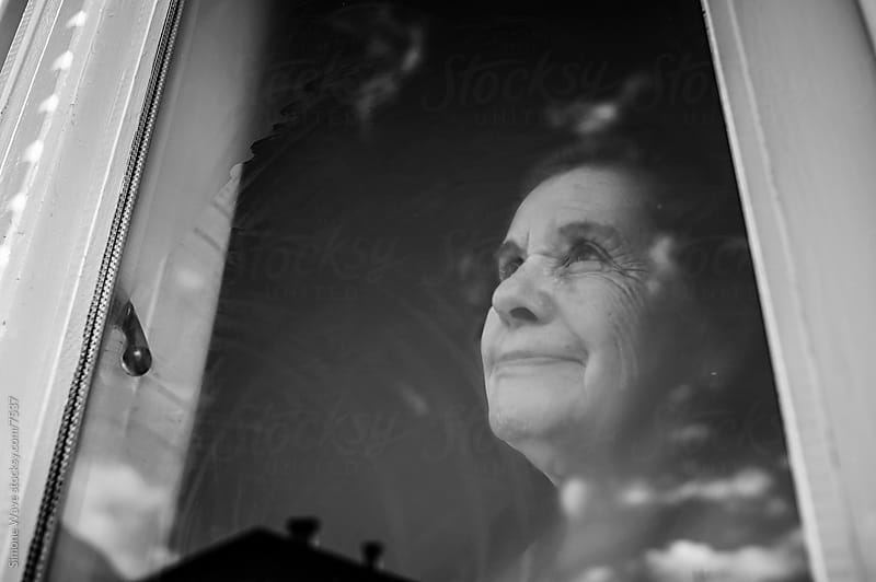 Senior woman portrait at window by Simone Becchetti for Stocksy United