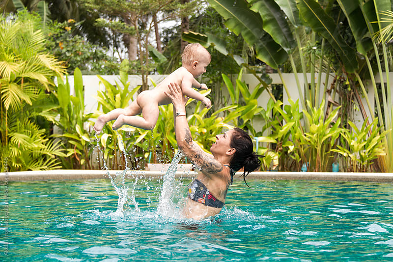 mum and her son having fun in the pool by Leander Nardin for Stocksy United