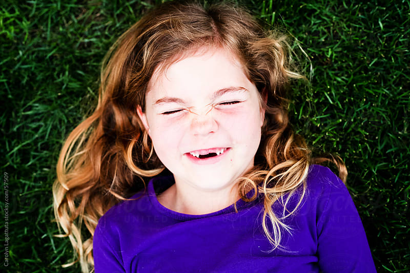 Missing two front teeth, laying in the grass and laughing by Carolyn Lagattuta for Stocksy United