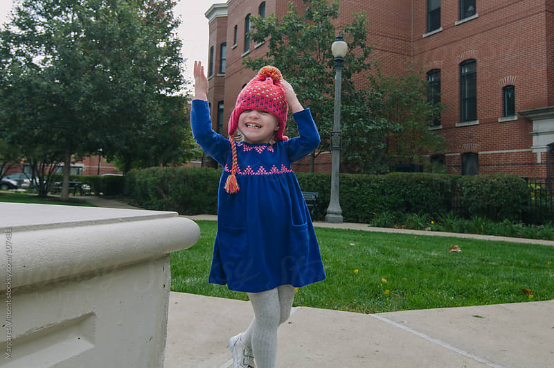 little girl puts on her own winter hat by Margaret Vincent for Stocksy United