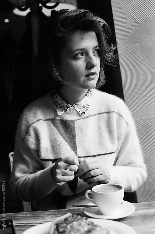 A black and white film portrait of young woman in coffeeplace by Anna Malgina for Stocksy United