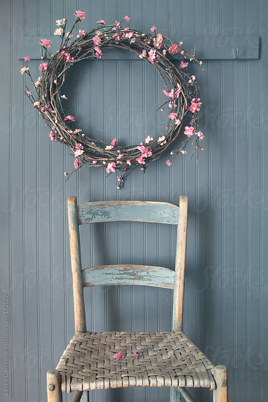 Apple blossom wreath hanging on coat hook with chair by Sandra Cunningham for Stocksy United