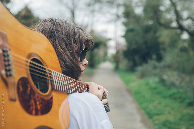 Young woman with a guitar outdoors  by kkgas for Stocksy United
