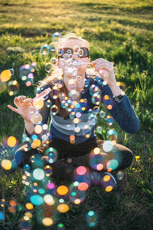 Young woman sitting on meadow grass blowing soap bubbles  by Ilya for Stocksy United