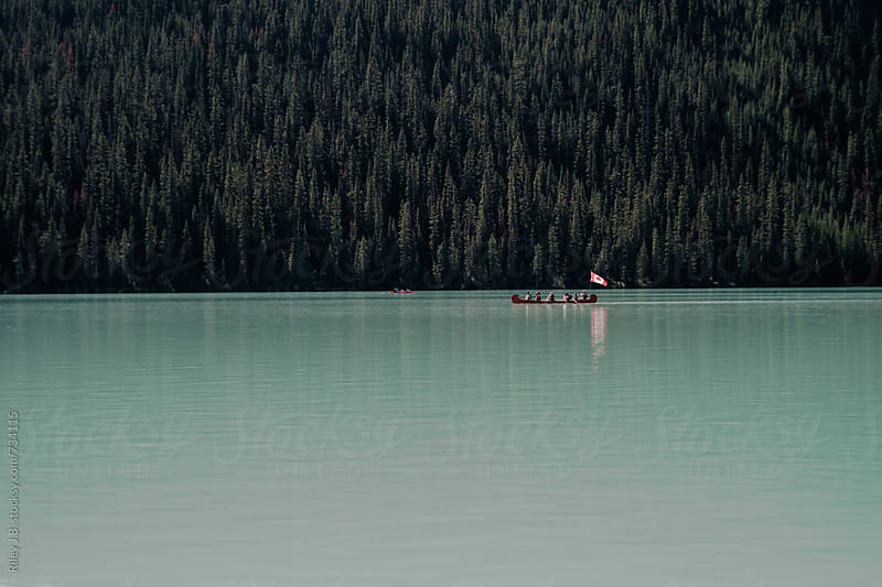 A canoe in a lake with a treed shoreline. by Riley J.B. for Stocksy United