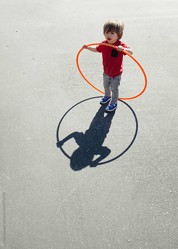 A boy with hula hoop outside. by Lucas Saugen for Stocksy United