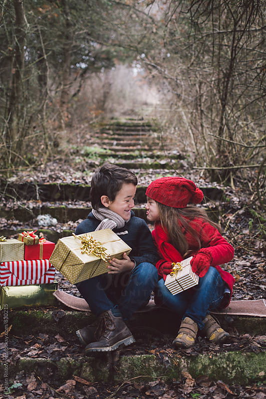 Children holding presents. by Dejan Ristovski for Stocksy United