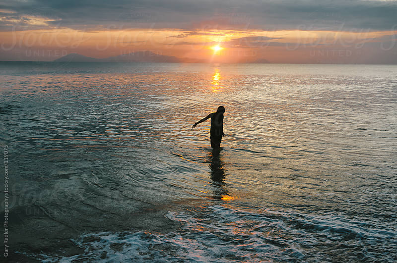 Girl in Sea at Sunrise by Gary Radler Photography for Stocksy United