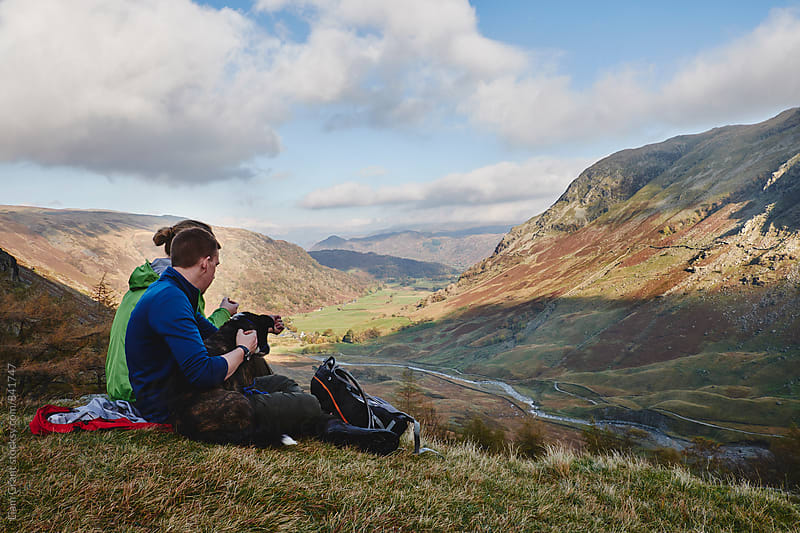 Young couple and their dog sat admiring the mountain view. Cumbria, UK. by Liam Grant for Stocksy United