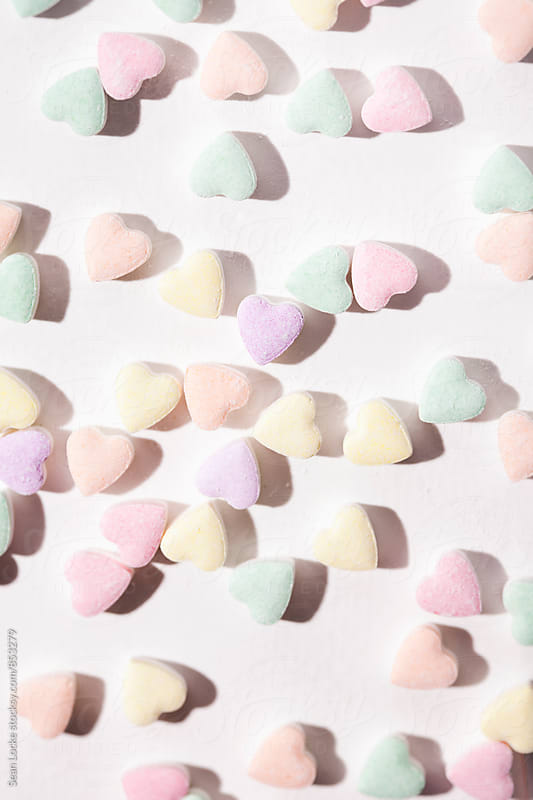 Valentine: Candy Hearts Scattered On White Paper by Sean Locke for Stocksy United