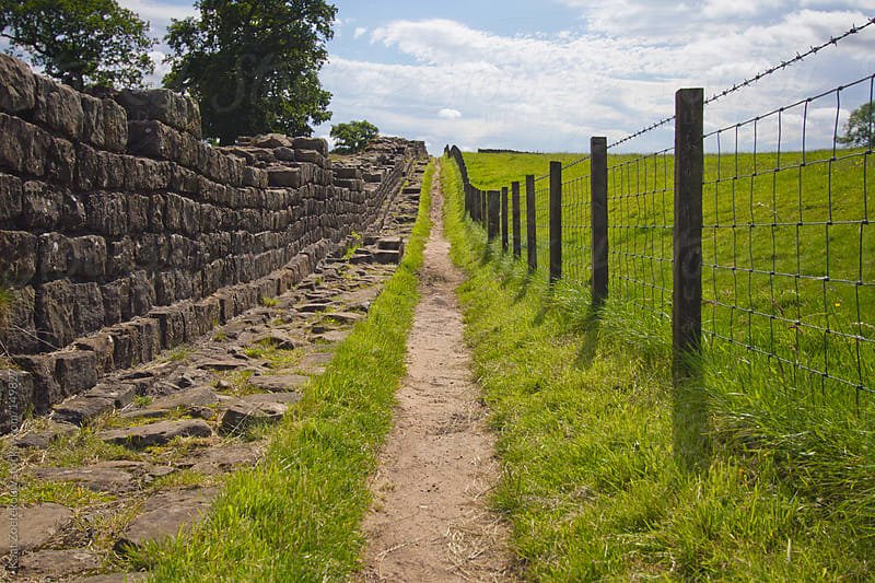 A pathway next to the sunlit remnants of Hadrian's Wall, UK. by Kaat Zoetekouw for Stocksy United