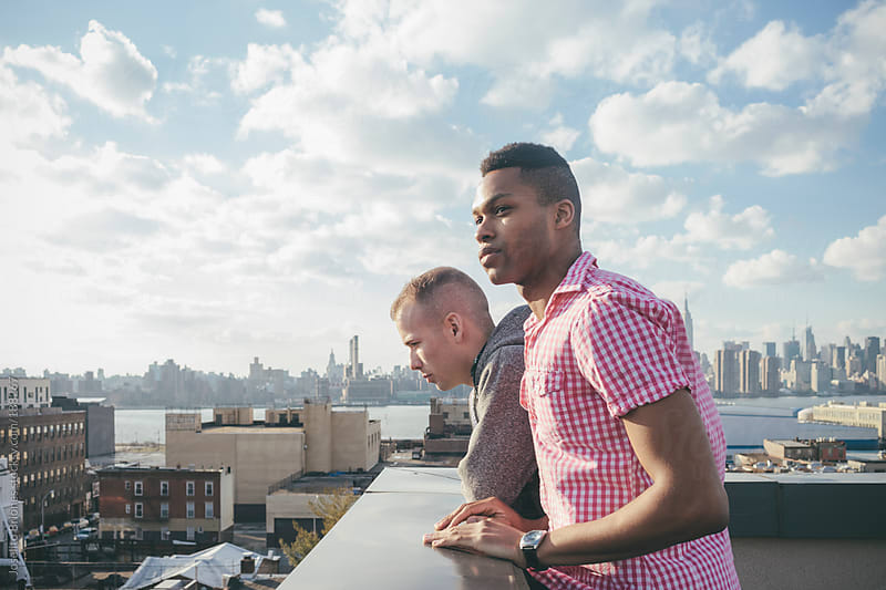 Friends Hanging Out on a Rooftop with New York Skyline by Joselito Briones for Stocksy United