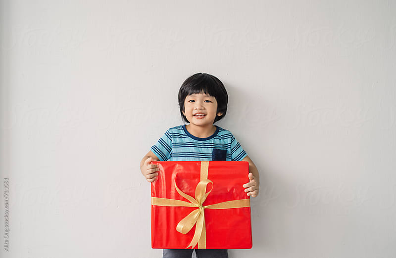 Little boy smiling carrying a gift box by Alita Ong for Stocksy United