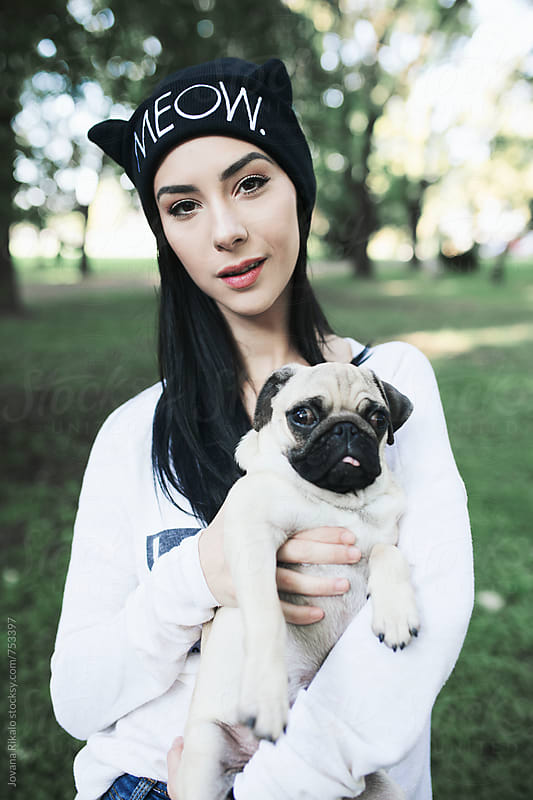 Portrait of a young woman and a pug dog by Jovana Rikalo for Stocksy United