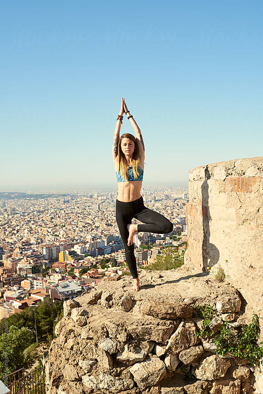 Woman on rocky edge in tree pose by Guille Faingold for Stocksy United