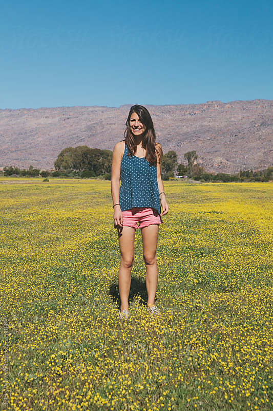 Attractive happy woman standing in a field of flowers by Micky Wiswedel for Stocksy United