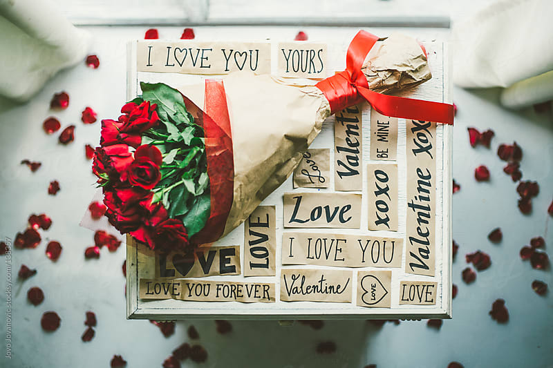 Valentine: bouquet of red roses on table with love messages around. by Jovo Jovanovic for Stocksy United