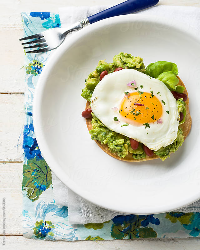 Delicious guacamole, egg, bean & cheese tostada  by Trent Lanz for Stocksy United