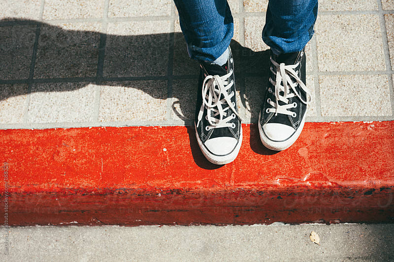 Black high top sneakers standing on a bright, red curb by Carolyn Lagattuta for Stocksy United
