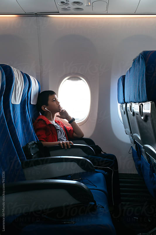 Young plane passenger sitting alone and enjoying the in-house movie by Lawrence del Mundo for Stocksy United