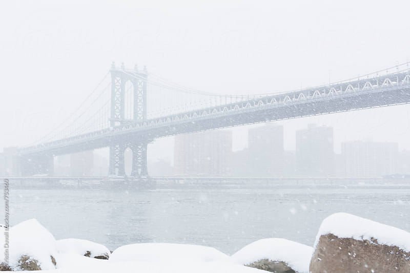 Manhattan bridge during snowstorm. New York City.  by Kristin Duvall for Stocksy United