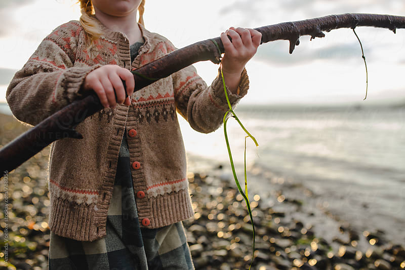 Little girl grasping a Large stick covered in Seaweed by Amanda Voelker for Stocksy United