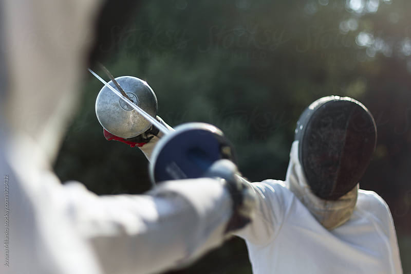 Man and a woman in fencing duel by Jovana Milanko for Stocksy United