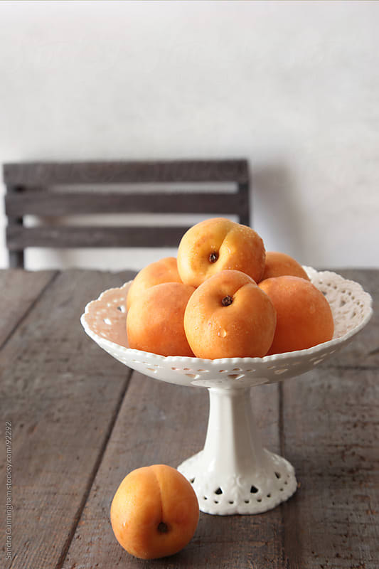 Fresh peaches on old brown table by Sandra Cunningham for Stocksy United