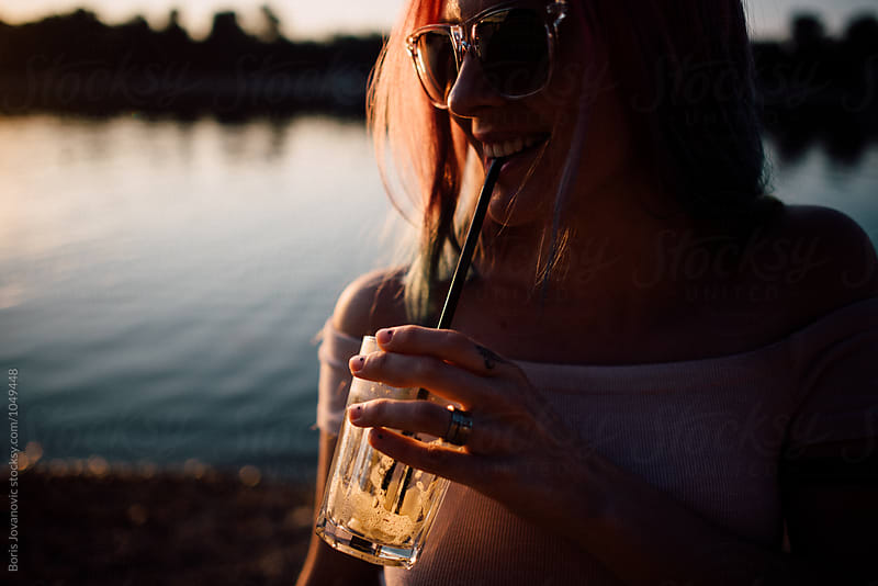 Young woman with drink outdoor by Boris Jovanovic for Stocksy United