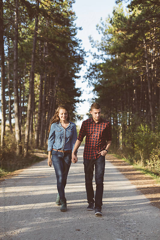 Couple walking trough the forest by Dejan Ristovski for Stocksy United
