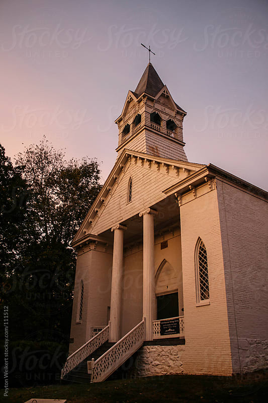 Old white church during a sunset by Peyton Weikert for Stocksy United