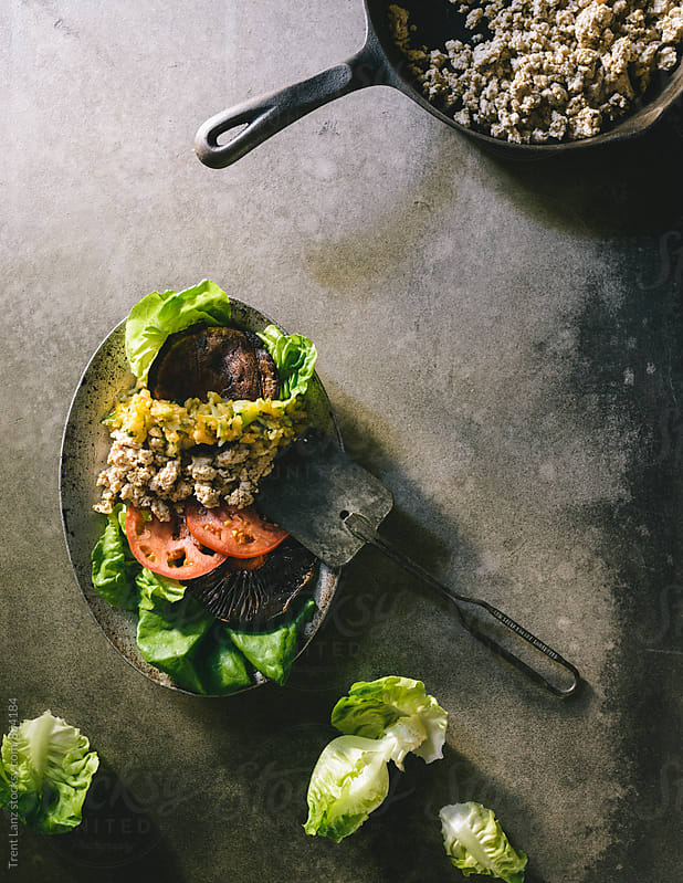Paleo firecracker Turkey Burger with Mushrooms Tomato & Lettuce by Trent Lanz for Stocksy United