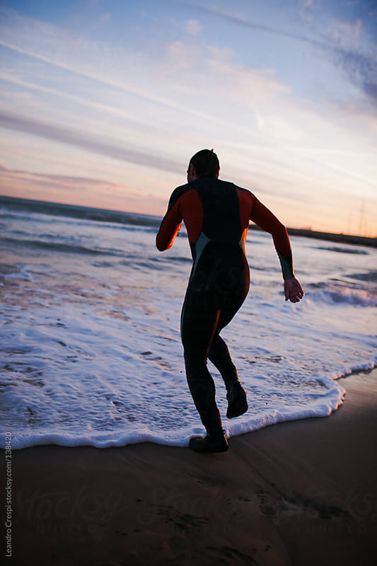 Man running into the sea with surfing suit by Leandro Crespi for Stocksy United