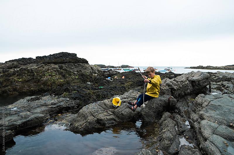 little boy fishing in a tidal pool.  by Léa Jones for Stocksy United