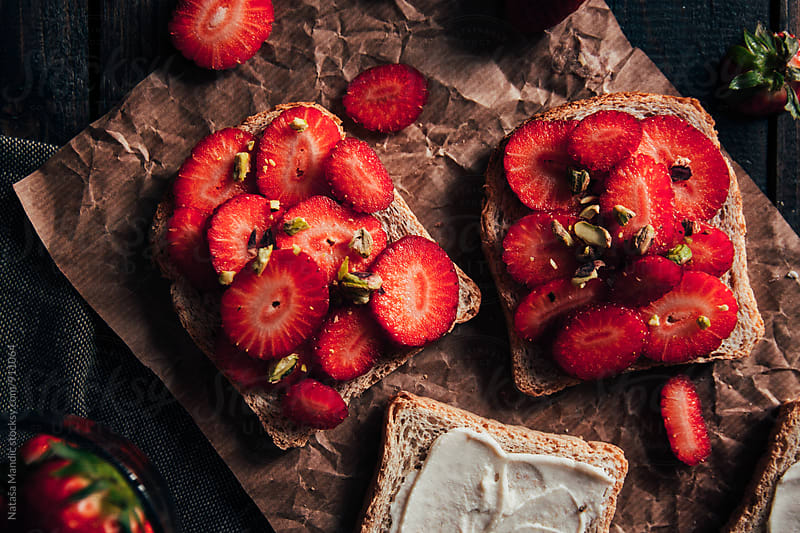 Strawberry toast with pistachio by Nataša Mandić for Stocksy United