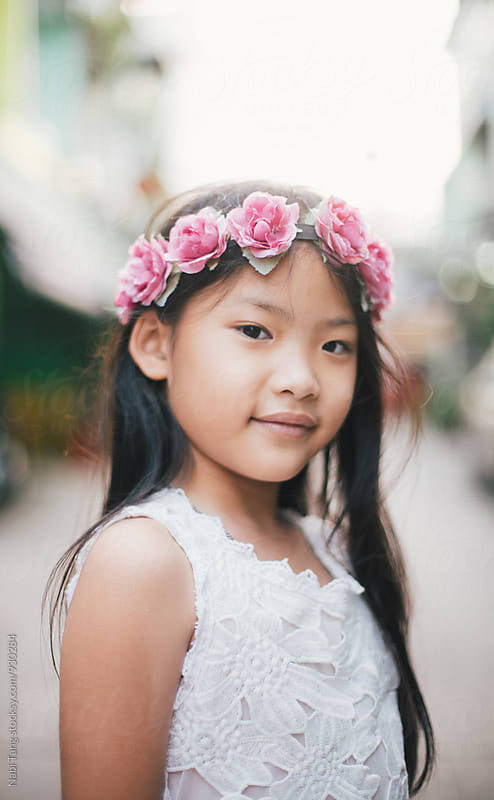 Beautiful Asian kid portrait with pink roses head band by Nabi Tang for Stocksy United