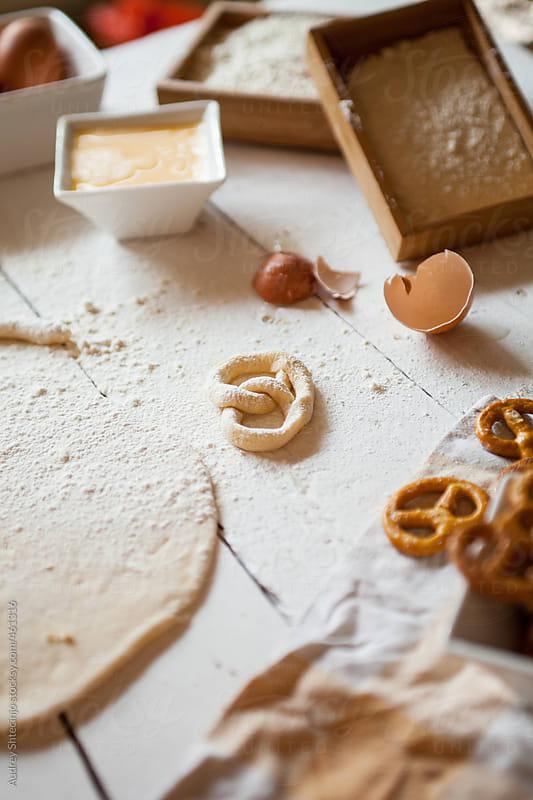 Making pretzels on white wooden table. by Audrey Shtecinjo for Stocksy United