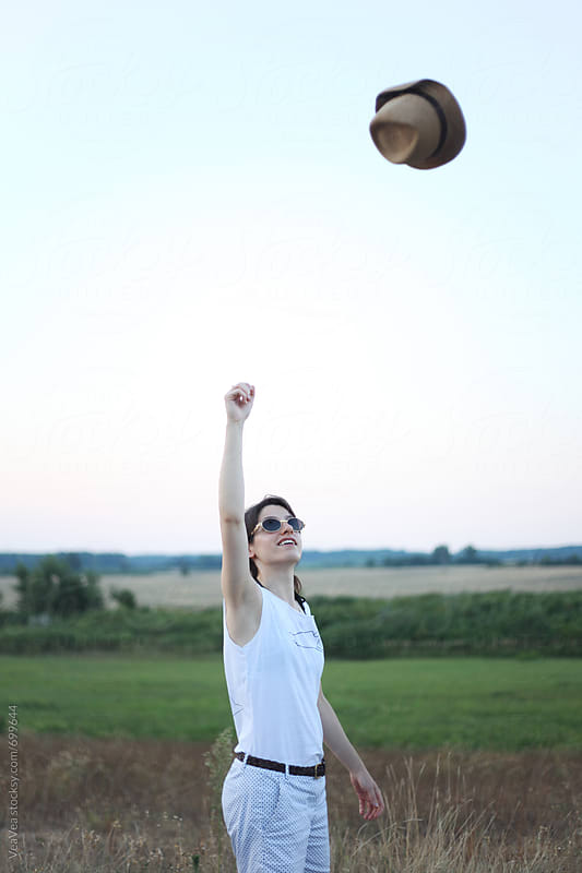 Happy young woman in nature throwing her hat in the air  by VeaVea for Stocksy United