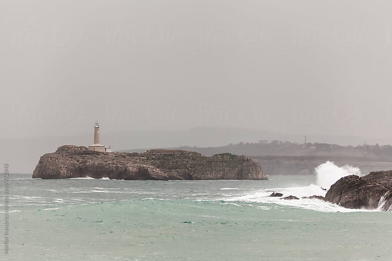 View of a lighthouse on a cloudy and rainy day by Marilar Irastorza for Stocksy United