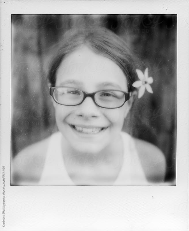 Black and white Polaroid portrait of girl with a flower in her hair by Carleton Photography for Stocksy United