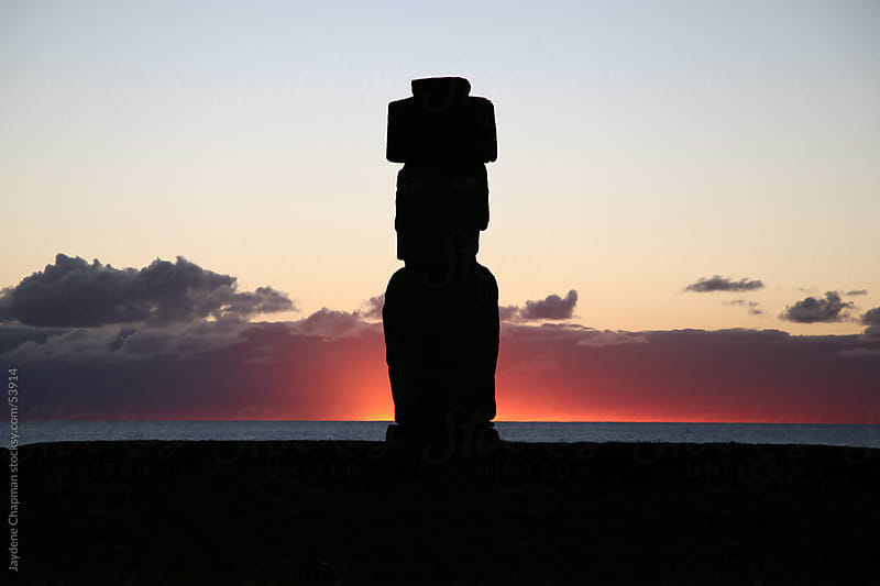 Vivid sunset going down behind a large stone Moai Statue, Easter Island Chile by Jaydene Chapman for Stocksy United